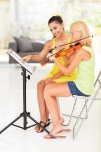 student receiving violin lesson