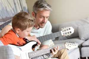 father and son learning guitar together
