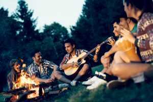 friends playing guitar around a campire