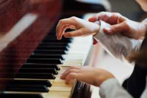 zoomed in teacher and student hands on a piano