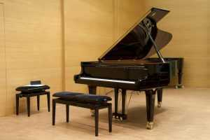 grand piano on stage with bench