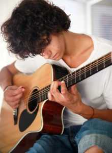 young man practicng guitar